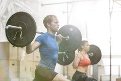 Barbells de elevación del hombre y de la mujer en gimnasio del crossfit Imágenes de archivo libres de regalías