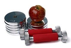 Barbells en appel die op wit wordt geïsoleerde Stock Foto