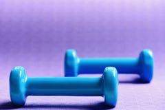 Barbells feitos do plástico, fim acima Pesos no azul ciano imagem de stock royalty free