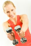 Barbells in hands. Photo of young woman showing two metal dumbbells Stock Photography