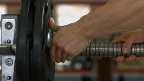 Barbells hanging on metal rack in gym hall. Training apparatus in gym. Barbells hanging on metal rack in gym hall stock video footage