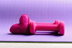 Barbells and pink love symbol, close up. Dumbbells made of pink plastic near soft toy heart on purple texture background, copy space. Love of sports and stock image