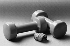 Barbells in small size next to cyan ruler, close up. Shaping and fitness equipment. Dumbbells made of green plastic near measuring tape roll on purple royalty free stock photos