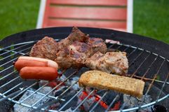 Barbeque. Meat, sausages and bread at the barbeque Royalty Free Stock Photo