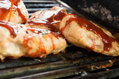 Barbeque chicken cooking on the grill Stock Photography