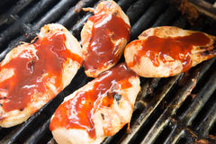 Barbeque chicken cooking on the grill Stock Photos