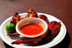 Barbeque chicken wings with chilly sauce. Barbeque chicken wings in a plate with chilly sauce and a lemon Stock Image