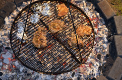 Barbeque. Cooking juicy steaks and potatoes in aluminum foil on a grillage over open charcoal fire Stock Photos