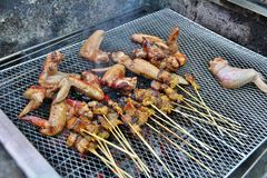 Barbeque. Delicious Chicken Wings and Satay being cooked during a barbeque Royalty Free Stock Images