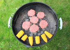 Barbeque grill with beef burger and corncob Royalty Free Stock Photo