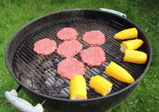 Barbeque grill with beef burger and corncob Stock Photo