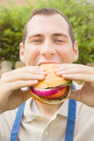 Barbeque: Man Eating a Hamburger stock images