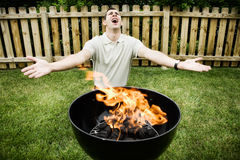 Barbeque: Man Prays to God of Fire Stock Photos