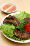 Barbeque pork chop. Ala carte grilled Pork Chop served on bed of lettuce with sauce Stock Photos