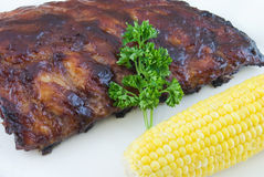 Barbeque Ribs. Barbecue baby back ribs with corn on the cob Stock Images