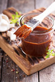 Barbeque sauce in a jar. Barbeque sauce with a basting brush in a jar stock images