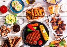 Barbequed肉和菜在野餐桌上 免版税库存照片