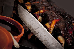 Barbequed beef ribs and corn. Beef ribs cooked on the barbeque and served with sweetcorn and a red wine souse stock image