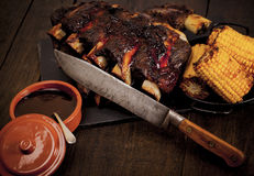 Barbequed beef ribs and corn. Beef ribs cooked on the barbeque and served with sweetcorn and a red wine souse royalty free stock photo