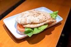 Barbequed chicken breast. With lettuce and tomato in bread stock photos