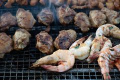 Barbequed food of satay, prawns and chicken wings royalty free stock photography