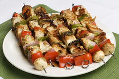 Barbequed kebabs on white plate. With green place mat stock photo