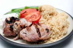 Barbequed lamb kebabs with grilled tomato, quinoa and tzatziki, Royalty Free Stock Images