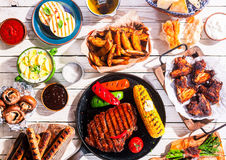 Barbequed Meats and Vegetables on Picnic Table. High Angle View of Grilled Meal - Appetizing Barbequed Meats and Vegetables Arranged on White Wooden Picnic Table Royalty Free Stock Photo