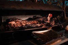 Barbequed Pig. On smoker grill with red apple in it`s mouth and foil covered pan in front Stock Photography