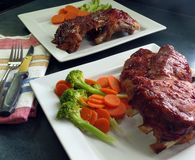 Barbequed Spareribs. Two servings of barbequed spareribs, hot from the oven, with broccoli and carrots stock photo