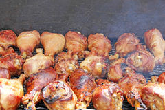 Barbequed Turkey Legs on Hot Grill. Barbequing turkey legs on grill at outdoor event royalty free stock image