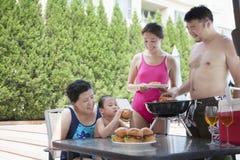 barbequing由水池的微笑的多代家庭在度假 免版税库存图片