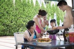 barbequing由水池的微笑的多代家庭在度假 库存照片