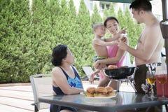 barbequing由水池的微笑的多代家庭在度假 免版税图库摄影
