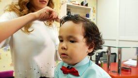 Barbería de los niños El estilista está peinando el pelo largo para el pequeño muchacho lindo Cierre para arriba metrajes