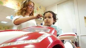 Barbería de los niños El niño pequeño que se sienta en coche y estilista del juguete se peina el pelo almacen de video