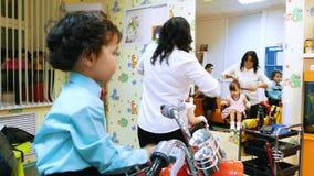 Barbería de los niños Niño divertido en salón de la peluquería Niño pequeño que se sienta en motocicleta del juguete metrajes
