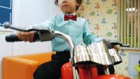 Barbería de los niños niño pequeño en la motocicleta del juguete metrajes