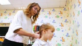 Barbería de los niños Peluquero con la pequeña muchacha rubia Niño divertido en salón de la peluquería Cola de caballo de la fija almacen de video
