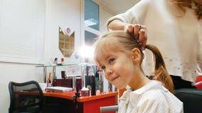 Barbería de los niños Peluquero con la pequeña muchacha rubia Niño divertido en salón de la peluquería Cola de caballo de la fija metrajes