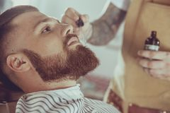The barber applies the beard oil with a dropper. Photo in vintage style royalty free stock photos