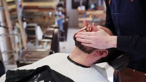 Barber applying beard styler to male face stock footage