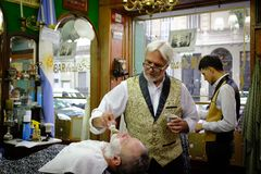2019-02-11 Argentina Session of haircut and shave of two men with two barbers royalty free stock photos