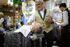 2019-02-11 Argentina Session of haircut and shave of two men with two barbers stock image