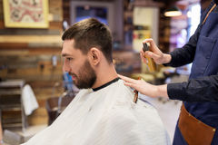 Barber applying styling spray to male hair at shop Stock Image