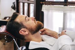 A barber attends to a customer in his barber shop royalty free stock images