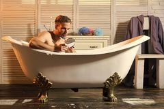 Barber, barbershop, shaving. Barber man shaving beard with vintage razor in bathtub royalty free stock photo