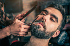 Barber beard cut a client's beard with clippers Stock Photo