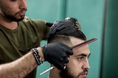 Barber in black gloves combs hair of stylish man at a barbershop royalty free stock image