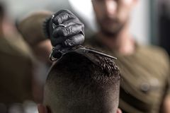 Barber in black gloves cuts with scissors hair on top of head of dark-haired man at a barbershop royalty free stock photos